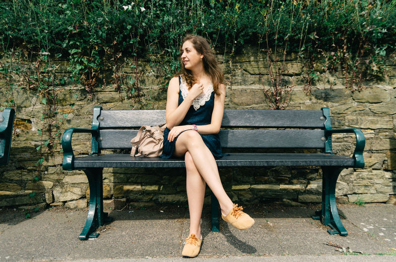 Young woman sitting on bench against retaining wall at park