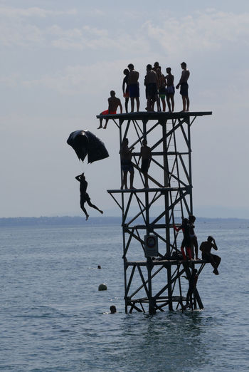 People on built structure in sea against sky