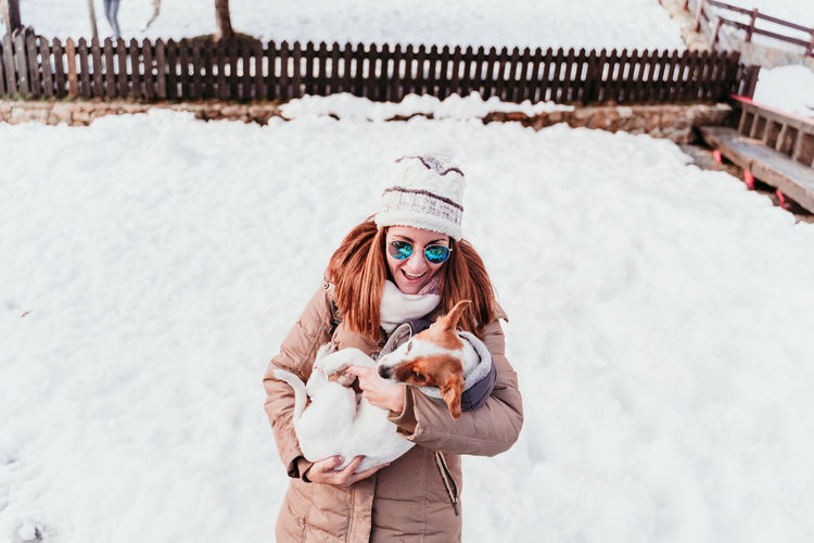 Cheerful woman carrying dog while standing on snowy land