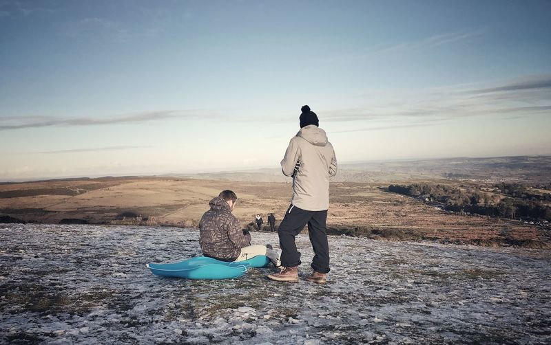 Rear View Of Man With Friend Sitting On Sled Against Landscape