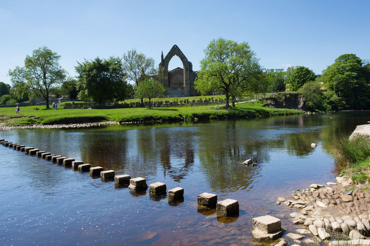 Stepping stones across the River Wharfe at Bolton Abbey, North Yorkshire, England, UK Bolton Abbey Copy Space Reflection River Wharfe Architecture Beach Blue Built Structure Day Growth History Lake Nature No Clouds Outdoors Plant Sky Stepping Stones Summer The Past Tranquil Scene Tranquility Tree Water