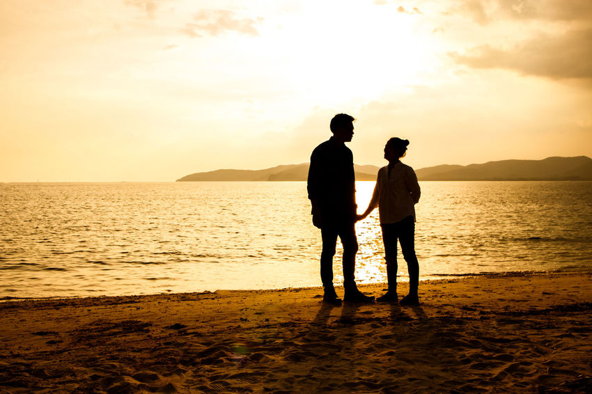 silhouette of people at the beach,The beauty of natural light at sunset. Sunset Sky Sea Water Beach Togetherness Land Two People Standing Silhouette Scenics - Nature Nature Beauty In Nature Men Real People Leisure Activity Full Length Bonding Love Positive Emotion Horizon Over Water Couple - Relationship Outdoors Silhouette Happiness Happy People Holiday Relaxing Children Women Man Romantic Orange Clouds And Sky Love Family Summer Sunrise Boy Freshair Freedom Fun