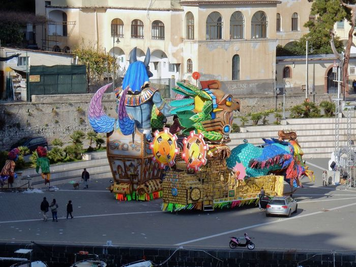 Maiori, Campania, Italy - March 4, 2019: Allegorical floats in the square of the port for the 46th edition of the Grand Carnival of Maiori Italy Campania Salerno Italy Grand Carnival Of Maiori Amalfi Coast Colorful Floats Carnival - Celebration Event Allegorical Floats Maiori, Day City Building Exterior Built Structure Real People Street Arts Culture And Entertainment Crowd Representation Multi Colored Celebration Leisure Activity Festival Carnival Outdoors