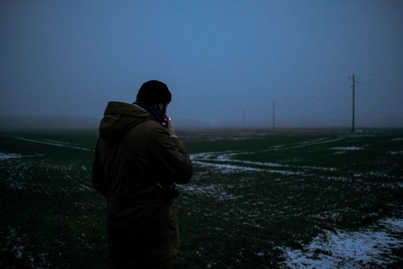 Man Smoking Cigarette While Standing On Field Against Clear Sky At Dusk