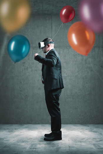 Side view of man holding balloon while using virtual reality simulator against wall