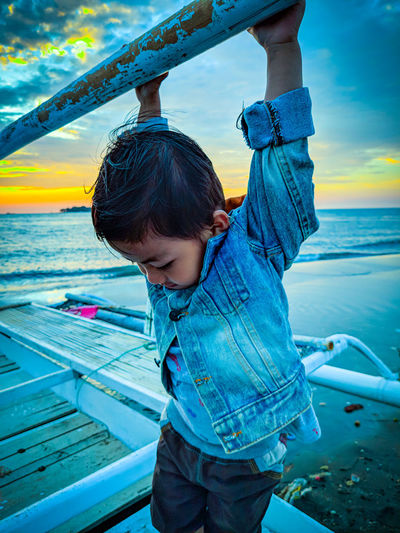 Boy hanging while holding rod against sea during sunset