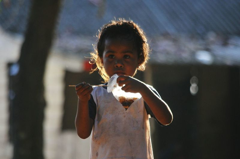 Girl Eating Food While Standing Outdoors