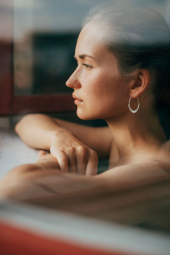 Close-up portrait of young woman looking out the window