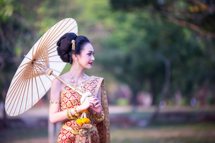Beautiful woman in traditional clothing looking away while holding paper umbrella