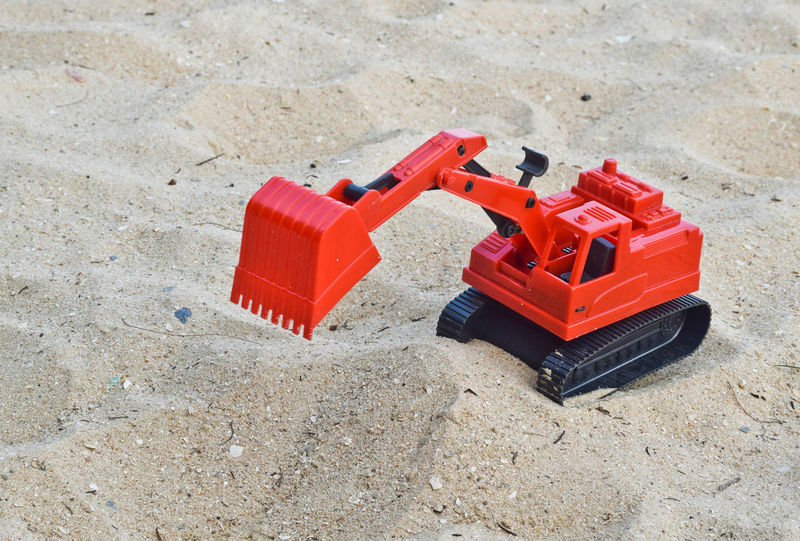 Children's toy red excavator car on sand,industrail symbols. Excavator Industrial Toy Transport Vehicle Bulldozer Construction Construction Site Machine Sandbox Tractor Beach Bucket Car Child Childhood Chrildren Excavation Hydraulic Industry Kid Model Outdoors Plastic Sand