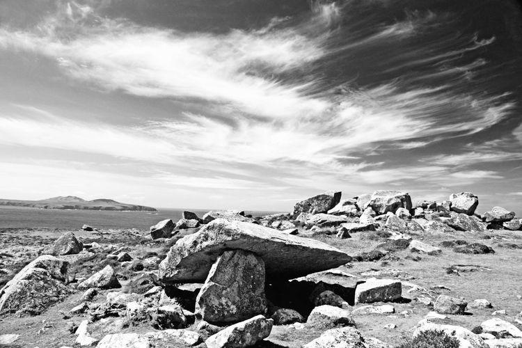 Rocks at on beach against sky