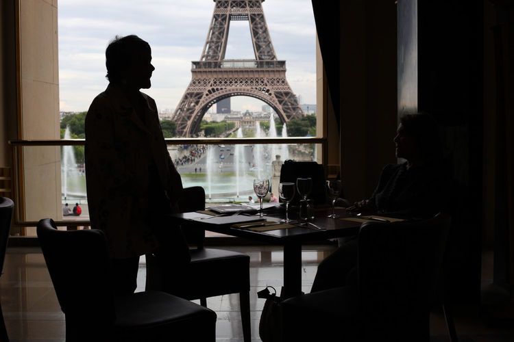 People in restaurant with view of Eiffel Tower