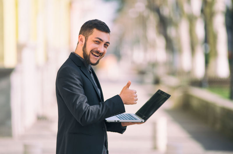 Well-dressed Business Person Businessman Focus On Foreground One Person Suit Corporate Business Formalwear Business Men Young Adult Young Men Males  Smiling Technology Standing Communication Waist Up Day Full Suit Wireless Technology Outdoors