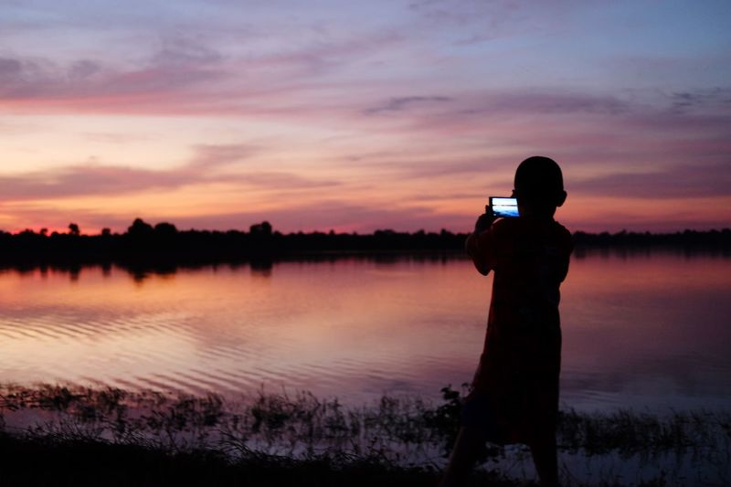 EyeEm Selects Sunset Silhouette Beauty In Nature Nature Real People Sky Scenics Photographing Outdoors Water Tranquil Scene One Person Reflection Tranquility Leisure Activity Lake Technology Tree Cloud - Sky Camera - Photographic Equipment Happiness Day Tranquility Silhouette Be. Ready.
