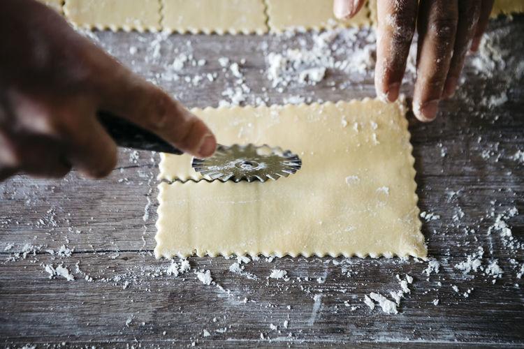 Cropped hands cutting ravioli dough