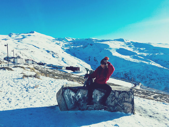 Man sitting on snow covered mountain