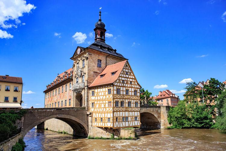Arch Bridge Over River Amidst Buildings Against Blue Sky