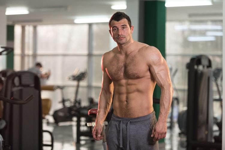 Full length of shirtless man looking at camera