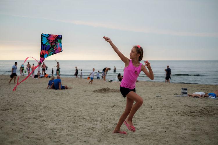 Full length of girl flying kite at beach during sunset