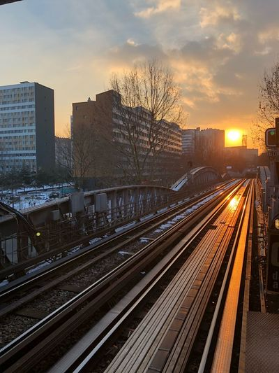 Railroad tracks by buildings in city during sunset