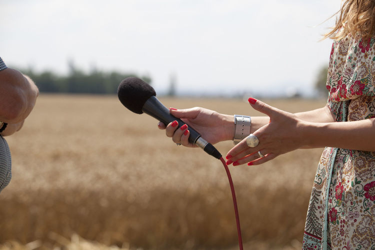 Midsection Of Woman Holding Microphone On Field