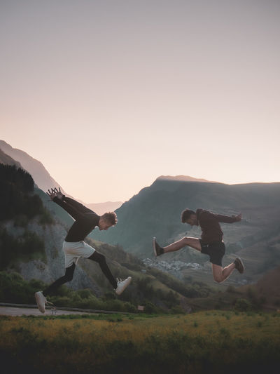 People playing on mountain against sky during sunset