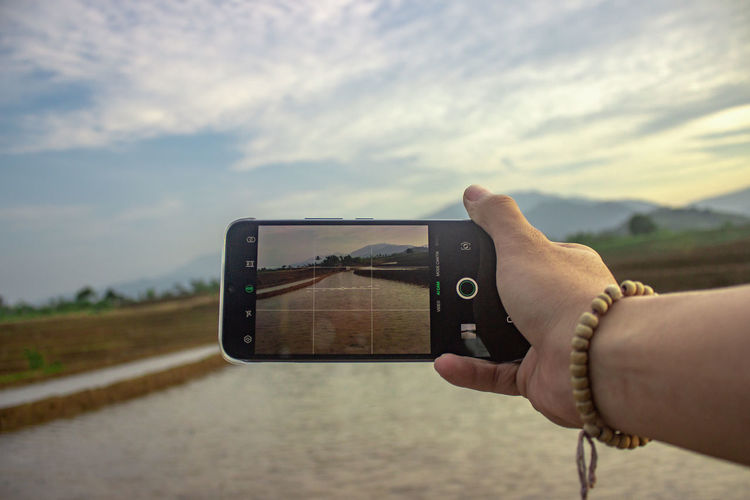 Man photographing camera on mobile phone against sky