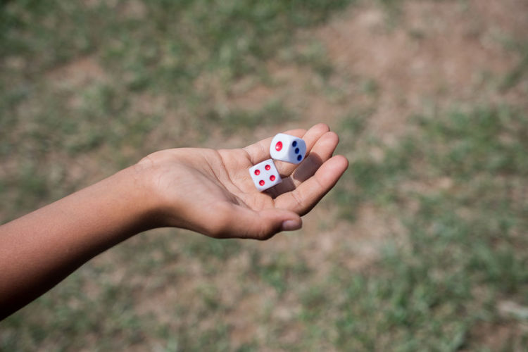 Cropped hand of person holding dice
