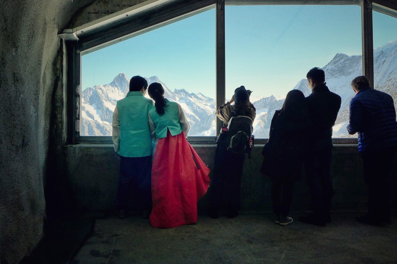 Rear view of people looking through window at observation point