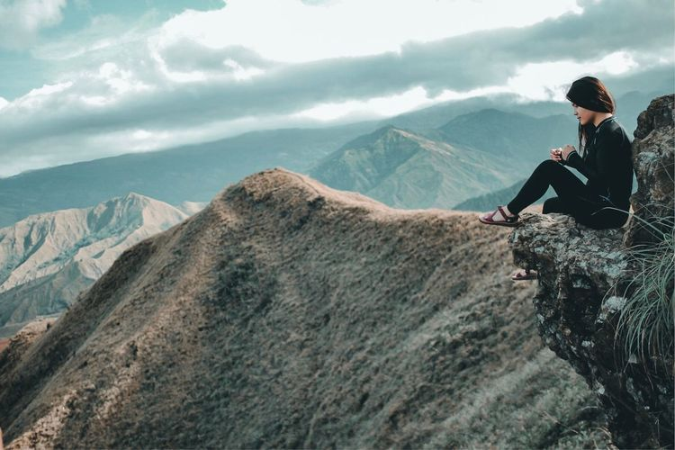 Side view of woman sitting on cliff against mountains
