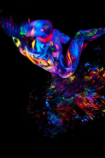 Close-up of multi colored light painting against black background