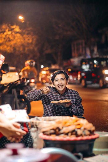 Woman holding ice cream on street at night