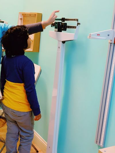 Annual health visit and doctor visit and pediatric medical visit One Person Real People Standing Rear View Casual Clothing Creativity Indoors  Three Quarter Length Holding Young Adult Wall - Building Feature DIY Lifestyles Women Working Occupation Waist Up Hairstyle Home Improvement Adult