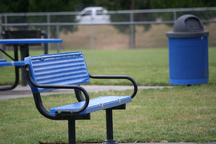 Empty blue bench on field in park