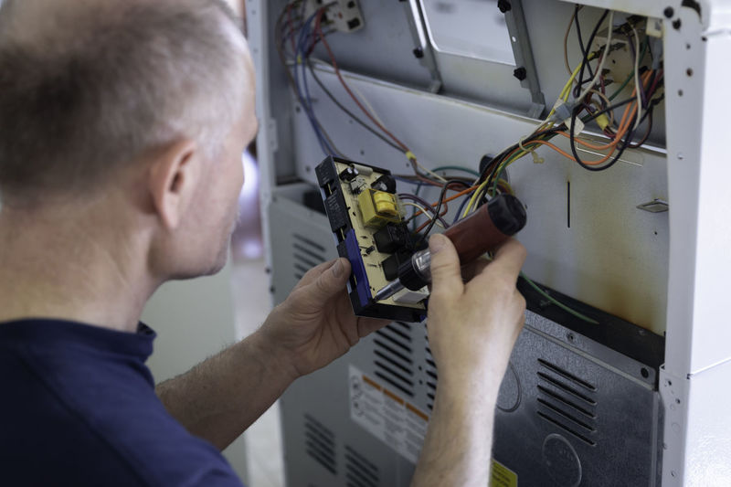 Close-up of man repairing electrical component