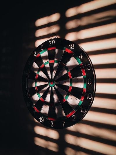 Dartboard on wall with shadow at home
