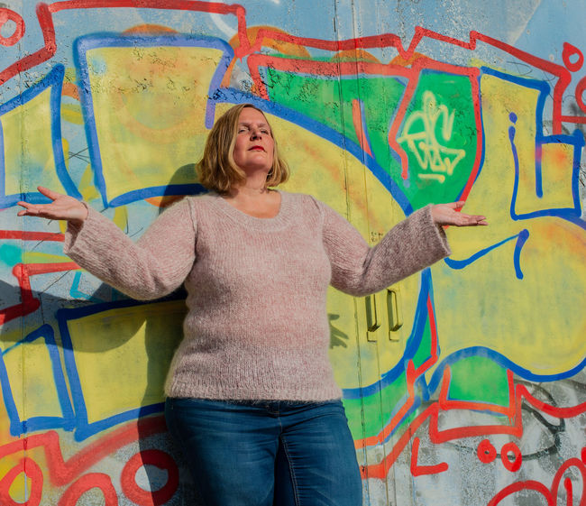 Posing of a model in a Pink Mohair Sweater in front of a graffiti wall Colors Fashion Graffiti Portrait Of A Woman Red Soft Winter Woman Aerosol Clothing Fashion Photography Fluffy Graffiti Wall Luxury Model Mohair Mohair Sweater Outerwear Portrait Posing Sprayer Trendy Warm