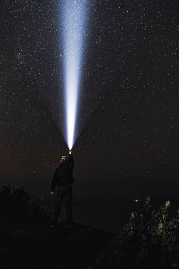 Low angle view of person against illuminated star field at night