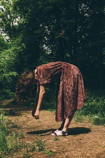 Full Length Of Woman Bending On Field Against Trees