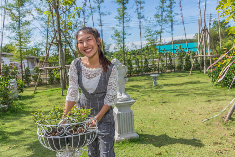 Smiling Woman Standing By Plants In Metal Planter
