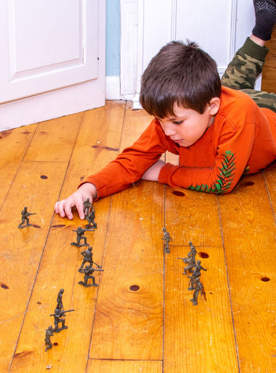 Child playing with toy army as he lies on a wood floor