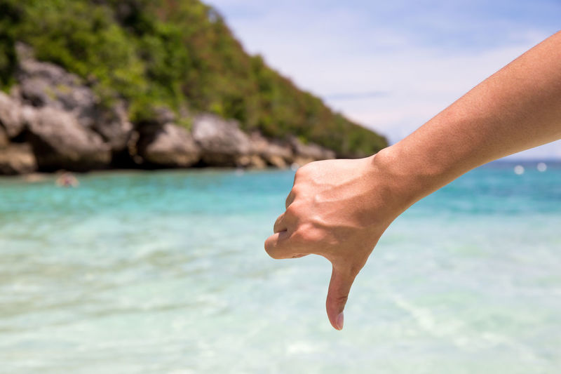 Close-up of hand showing thumbs down against sea
