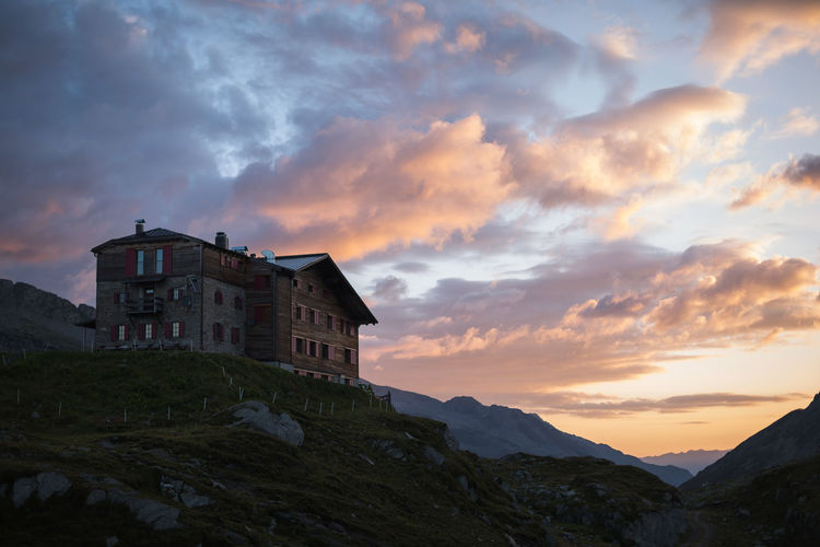 Low Angle View Of House And Mountains Against Sky During Sunset