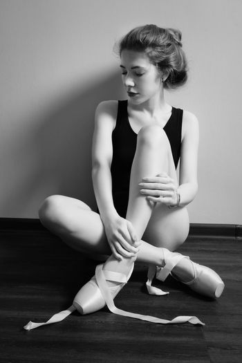 Woman looking away while sitting on wooden floor