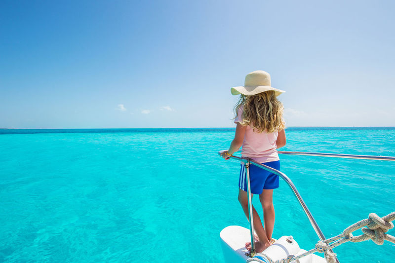 Beauty In Nature Blue Clear Sky Day Full Length Hat Horizon Over Water Leisure Activity Lifestyles Nature One Person Outdoors Rear View Sea Sky Standing Summer Sun Hat Sunlight Vacations Water
