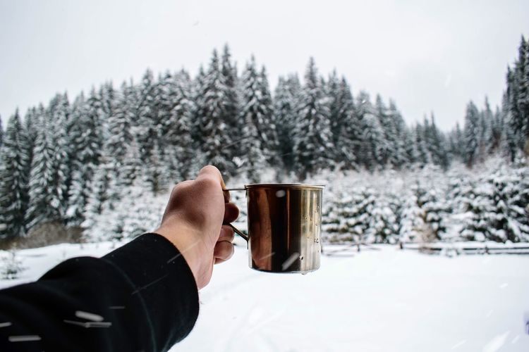Cropped hand holding mug during winter