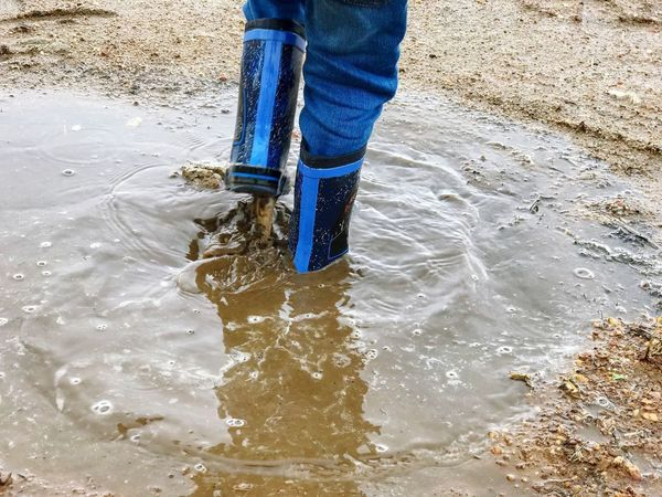 Dirty Water  Weather Raining Rainy Days Rain Boy Leg Play Enjoyment Enjoy Gum Boots Gumboots Boots Puddle Nature Environment Lifestyles Real People Child Low Section Childhood Water Real People Outdoors Blue Motion One Person Standing Human Body Part People
