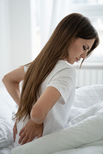 Woman suffering from muscle back pain has low lumbar muscular kidney pain after sleep sitting on bed