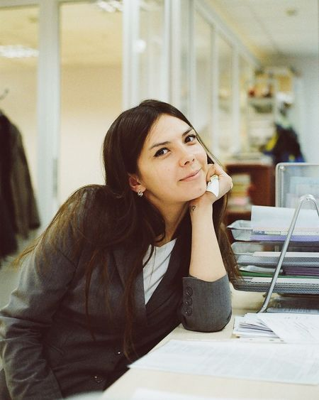Portrait of businesswoman sitting by desk at office