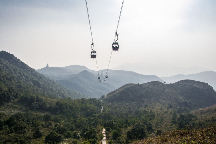 View of overhead cable car over mountains against sky